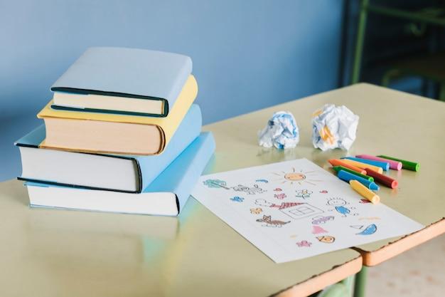 Posto di lavoro della scuola con libri e disegno