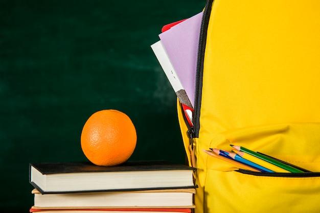 通学かばん、本の山とオレンジ