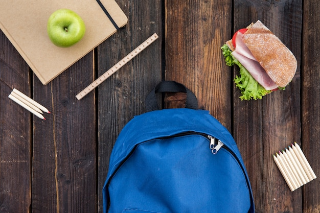 Schoolbag, sandwich and stationery on table
