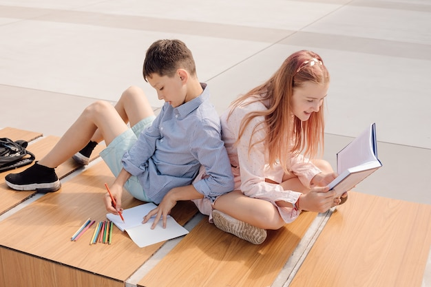 Школьник и школьница сидят спиной к спине на скамейке во дворе школы возле здания школы. учиться по книгам и тетрадям