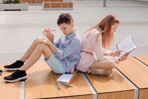 Школьник и школьница сидят спиной к спине на скамейке в школьном дворе возле здания школы. учиться по книгам и тетрадке