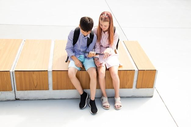 남학생과 여학생 10대들은 학교 운동장에 앉아 온라인 교육 개념을 통해 온라인 수업을 받습니다.