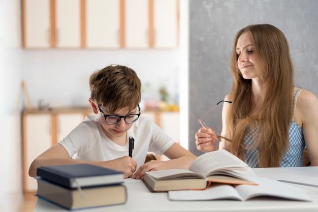 男子生徒と先生は本を読んでいます。若い母と息子は一緒に宿題をしています。家庭教師は学生と協力します。