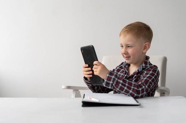 Schoolboy blond sits on a chair in front of the table. distance learning and quarantine. the child has a tablet in his hands and a notebook for writing on the table.