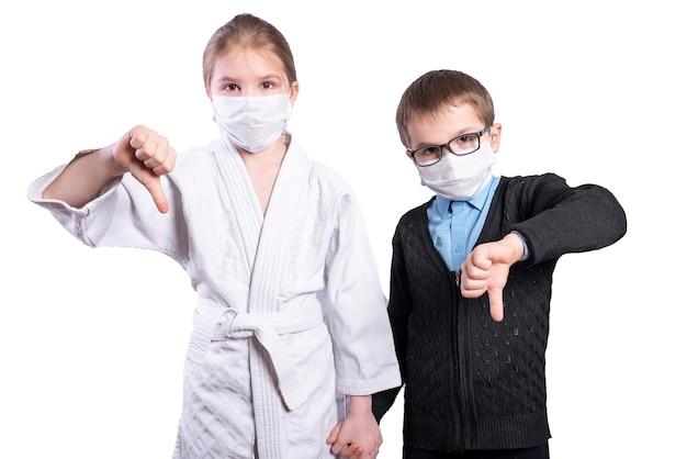 남학생 소년과 소녀 운동 선수는 아래로 엄지손가락을 보여줍니다. 마스크. 흰색 배경에 고립. 고품질 사진