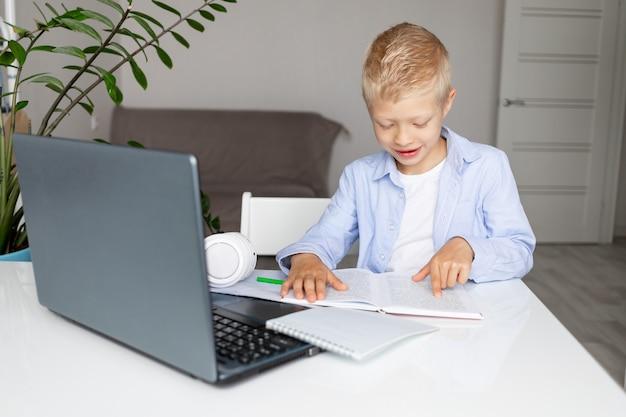모범생 소년 금발 노트북을 통해 집에서 원격 학습하는 동안 책을 읽고, 다시 학교로 개념을 배운다