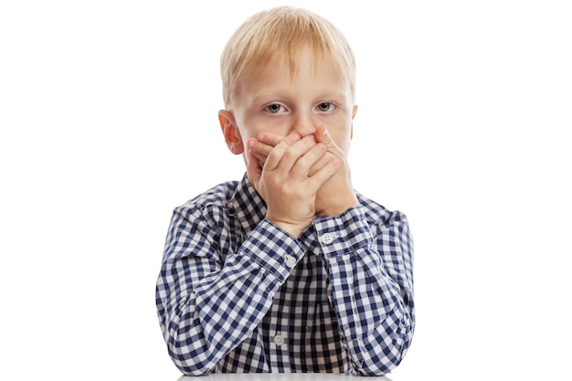 A schoolboy boy in a blue plaid shirt covered his mouth with his hands.