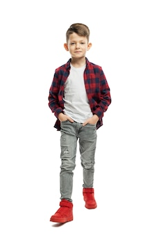 Schoolboy boy in jeans and a shirt goes forward. back to school. isolated on white background. vertical.