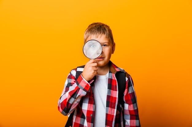 돋보기를 통해 보고 노란색 배경에 그의 눈을 확대 하는 모범생 소년
