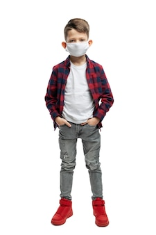 Schoolboy boy in a medical mask in gray jeans and a red plaid shirt