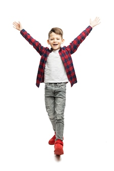 Schoolboy boy rejoices raising his hands up. full height. isolated on white background. vertical.