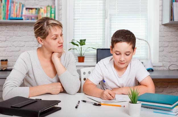 男子生徒は家で勉強し、学校の宿題をします。家庭用遠隔学習、オンライン児童教育、ホームスクーリング。隔離と社会的距離の概念。