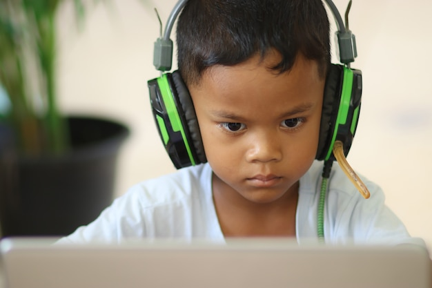 Schoolboy boy studies online on a laptop at home. communicates online with a teacher. teaches lessons from school at the computer. participates in distance education.