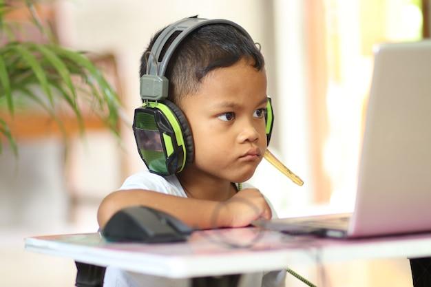 男子生徒は自宅のラップトップでオンラインで勉強します。教師とオンラインで通信します。コンピューターで学校からのレッスンを教えます。遠隔教育に参加します。