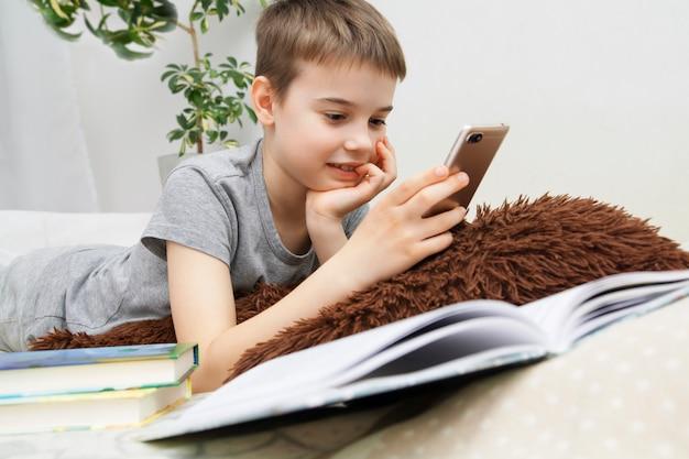 彼の手に電話を持つ男子生徒の少年。スマートフォンでのコミュニケーションや勉強。遠隔学習、ベッドでのコミュニケーション。