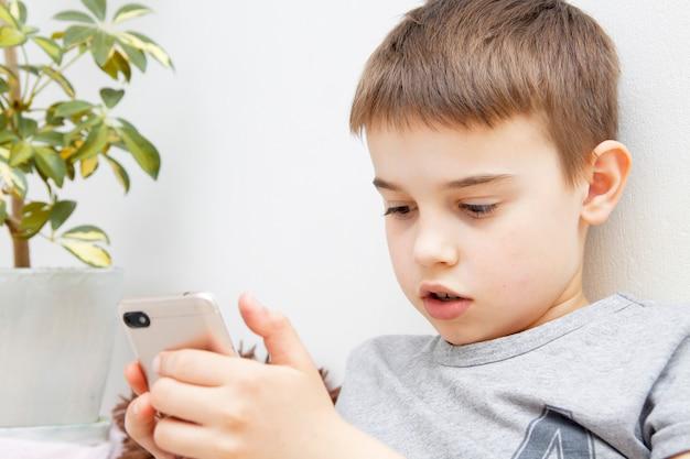 그의 손에 전화 모범생 소년입니다. 스마트 폰과의 커뮤니케이션 또는 학습. 원격 학습 온라인.