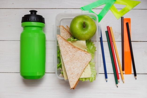Schoolboy breakfast on white wooden table.sandwich with cheese and ham and lettuce leaf, green bottle of water. rulers and pencils