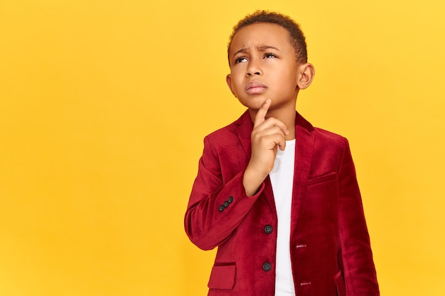 Schoolboy in bright velvet jacket looking up with pensive doubtful facial expression