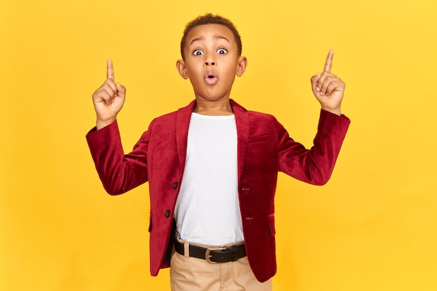 Schoolboy in bright velvet jacket pointing up