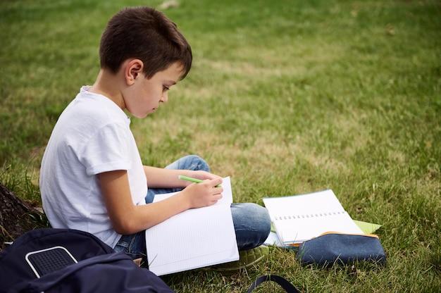 男子生徒は宿題をすることに集中し、前景に学用品とワークブックが入ったバックパックが入った筆箱の隣の都市公園の緑の芝生に座っていました。学校のコンセプトに戻ります。