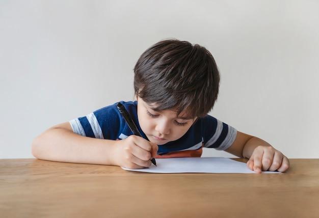 自宅で彼の宿題をしている少年