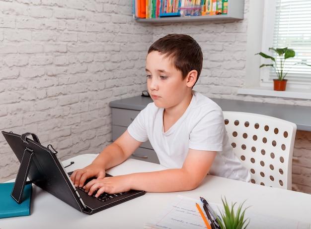 ラップトップコンピューターを自宅でノートブックで彼の宿題をしている少年