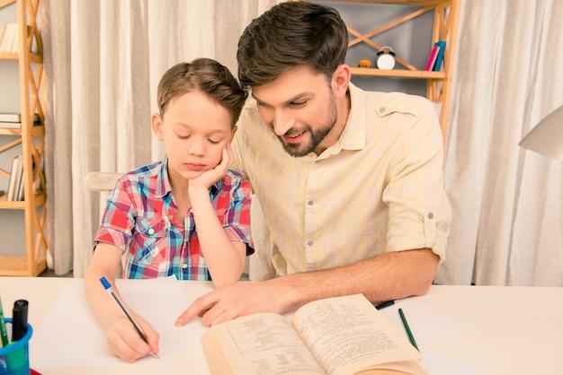父親と一緒にホームタスクをし、ワークブックに書いている男子生徒