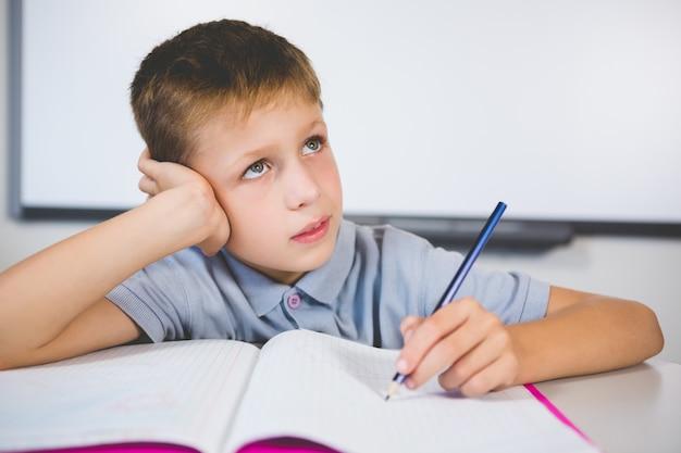 Schoolboy doing homework in classroom