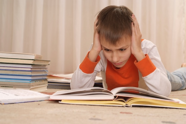 Школьник делает домашнее задание на полу дома