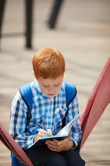 Школьник делает домашнее задание на открытом воздухе