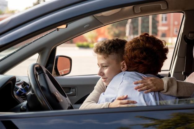 Школьник обнимает свою мать в машине перед школой