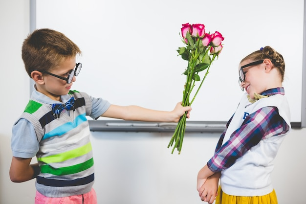 Schoolboy giving a bunch of flowers to a girl in classroom