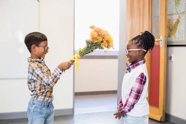 Schoolboy giving a bunch of flowers to a girl