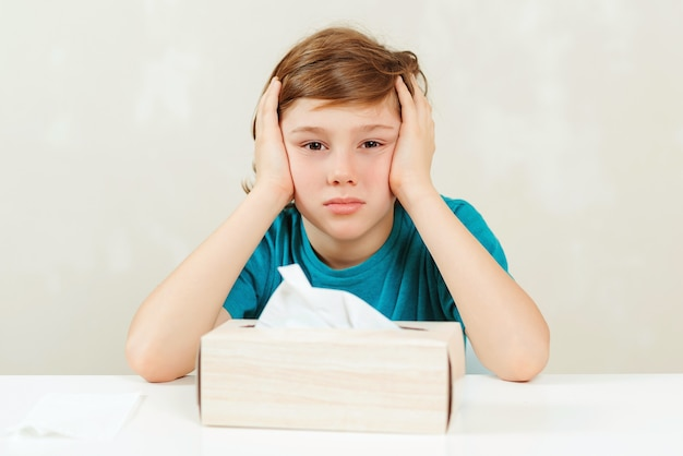 Schoolboy has headache during lessons. sick boy sitting at the desk.