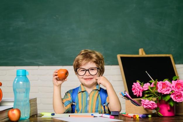 男子生徒は休憩時間に昼食をとる学校の生徒で食べるかわいい子供はで健康的な昼食の男の子を楽しむ