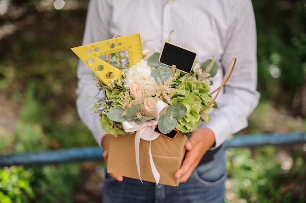 Школьник держит в руках праздничную коробку с цветами, украшенную линейкой