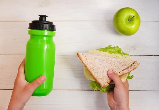 学校の朝食、サンドイッチ、水のボトル、グリーンアップルを保持している男子生徒