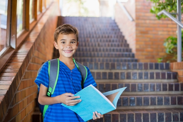 Schoolboy holding a book on staircase