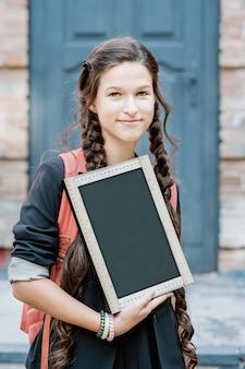 A schoolboy holding a chalk board