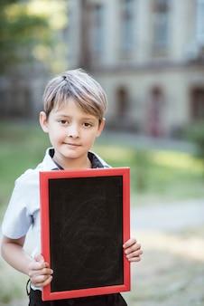 A schoolboy holding a chalkboard.