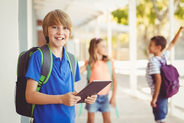 Schoolboy holding digital tablet in school corridor