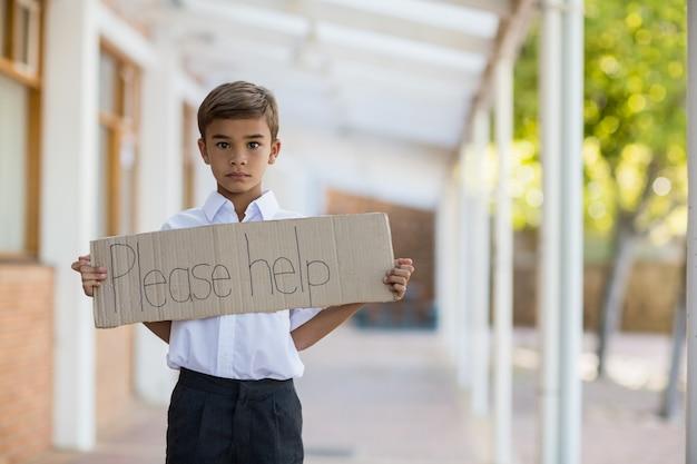 読んでいる少年がプラカードを持っているのを助けてください