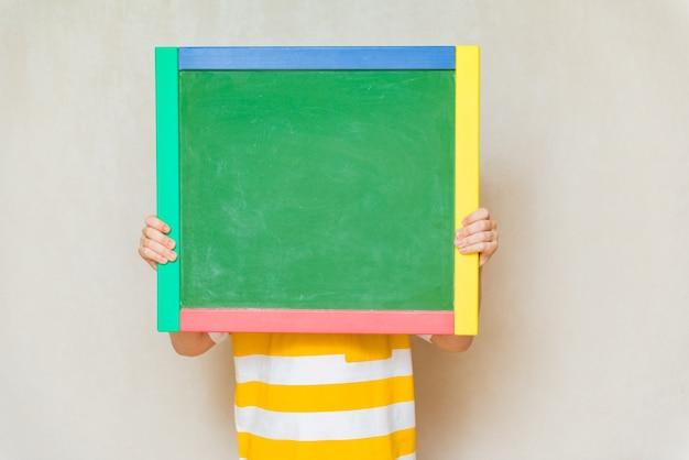 Школьник держит школьную доску копией пространства для текста