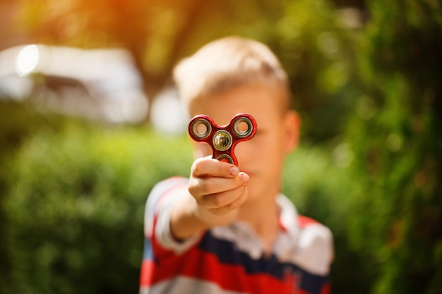 Schoolboy holds a spinner fidget in his hands. trendy and popular toy for children and adult.