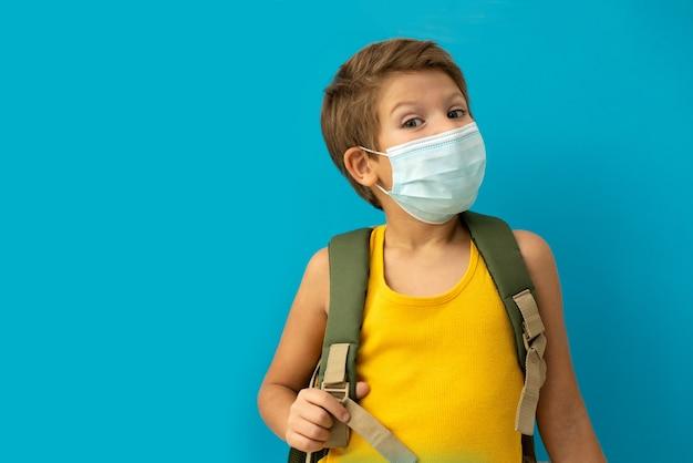 バックパックと医療マスクの男子生徒。学校に戻る。
