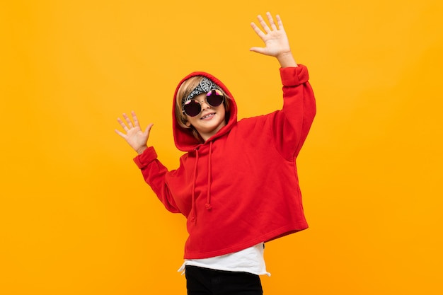 黄色の表面の上で踊って赤いセーターの男子生徒