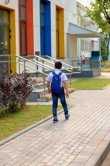 Школьник в белой рубашке и синем рюкзаке идет в школу