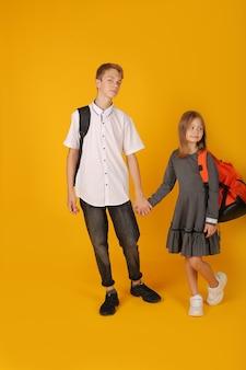 Школьник в белой рубашке и серых брюках держит за руку младшую сестру в школьном сером