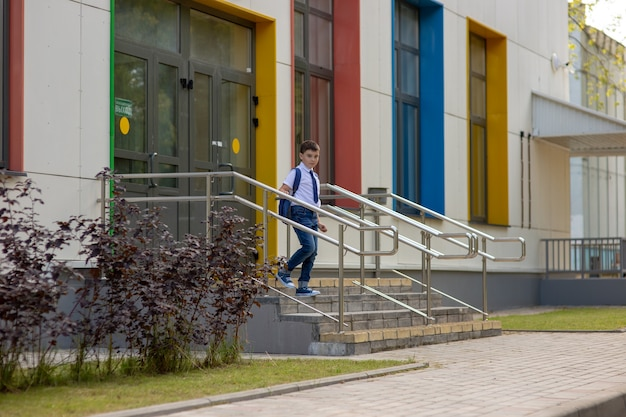 白いシャツ、青いネクタイ、バックパックを着た男子生徒が学校の階段を下る
