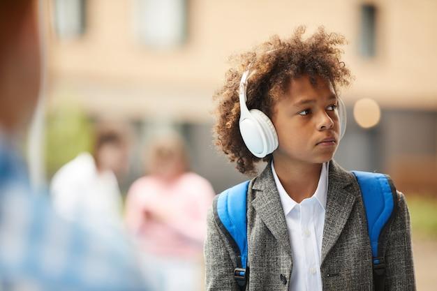屋外のヘッドフォンで男子生徒